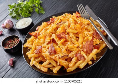 french fries with melted mix of shredded cheese and bacon served on a plate on a black wooden table with Ranch Dressing in a gravy boat, view from above, close-up