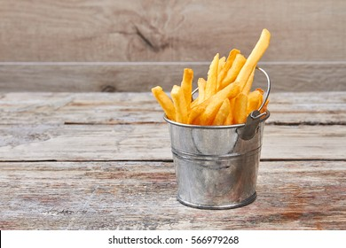 French fries in metal bucket. Fries on grunge wooden backdrop. Traditional british dish.