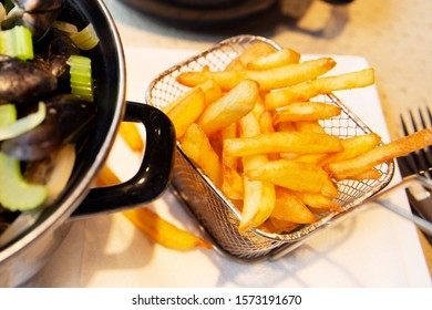 French fries with mussels in a pan on a cafe table. Traditional european food. Close-up.