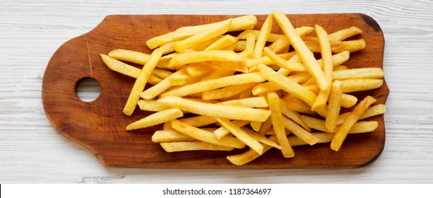 French fries on rustic wooden board on a white wooden background, top view. From above, flat, overhead.