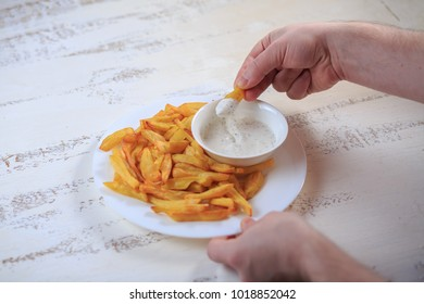 French fries on a table on a light table with sauce.