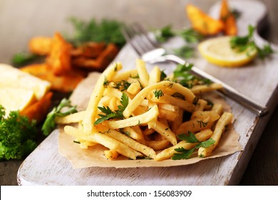 French fries on tracing paper on board on wooden table