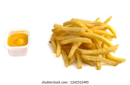 French fries on a white background. A pile of finished french fries close-up on a white background. Near the plastic container with cheese sauce.