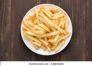 French fries on white dish on wooden background.