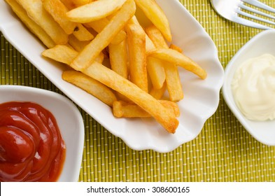 French fries on a white plate with mayonnaise and ketchup