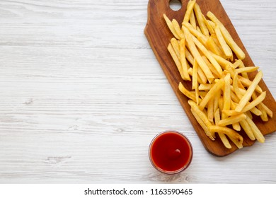 French fries on wooden board and ketchup over white wooden background, top view. From above, flat lay, overhead. Copy space.