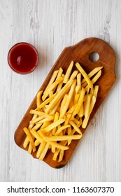 French fries on wooden board and sauce over white wooden table, overhead view. From above, flat lay.