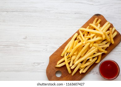 French fries on wooden board and sauce over white wooden background, overhead view. From above, flat lay. Copy space.