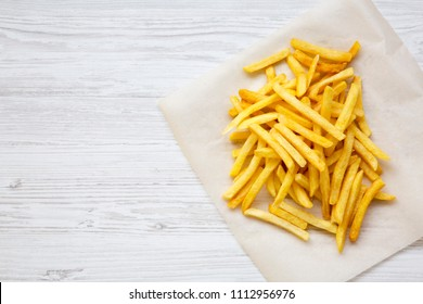French fries over white wooden background, from above. Copy space.