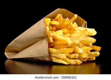 French fries in the paper bag isolated on black desk