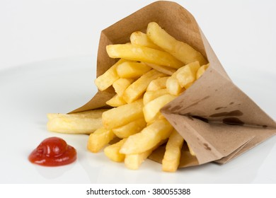 French fries in a paper bag with ketchup isolated on white
