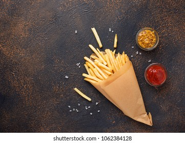 French fries in a paper bag with sauces. Top view