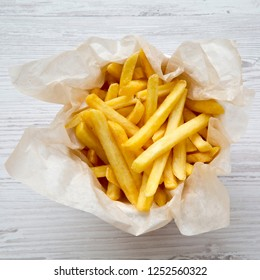 French fries in paper box over white wooden background, top view. From above, overhead.