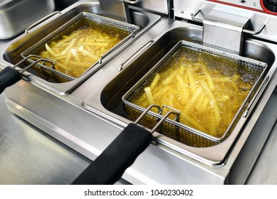 French fries or potato chips deep frying in oil in a commercial metal fryer in a restaurant as an accompaniment to meals