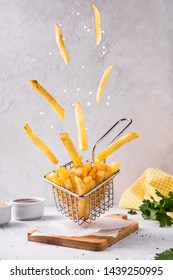 French fries potato with salt flying in basket. Fry delicious snack, fly food.