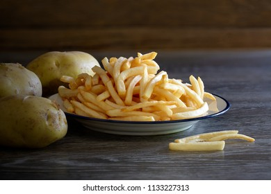 French fries and raw potato on wooden table in dim light / Still Life image and space for texts