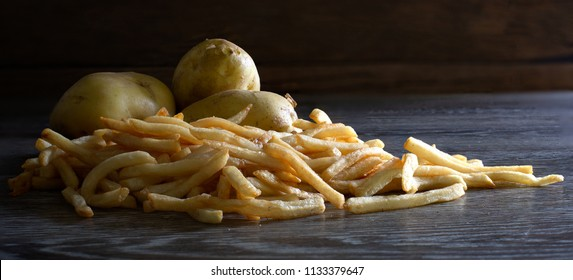 French fries and raw potato on wooden table in dim light  Still Life image and adjustment size  for cover, banner, header, with space for texts
