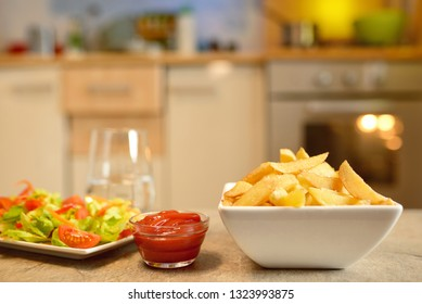 French fries and salad on table in kitchen