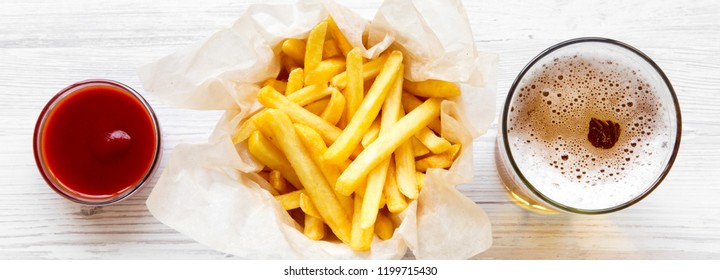 French fries with sauce and beer on a white wooden background, overhead view. Close-up.