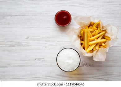 French fries with sauce and cold beer on a white wooden surface, top view. From above. Copy space.