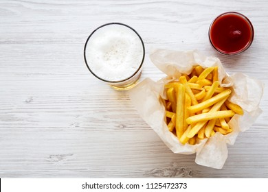 French fries with sauce and cold beer on a white wooden table, top view. From above, overhead. Space for text.