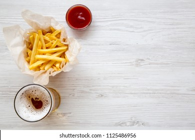 French fries with sauce and cold beer on a white wooden table, view from above. Top view, overhead. Copy space.
