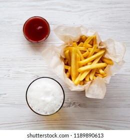 French fries with sauce and cold beer on a white wooden table, overhead view. From above, top view.