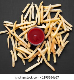 French fries with sauce on a black background, overhead view. Top view, flat lay.
