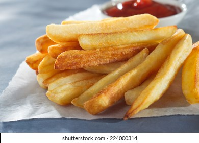 French fries with sauce on parchment.