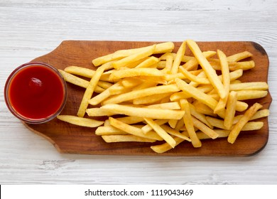 French fries with sauce on wooden board over white wooden surface, top view. From above.