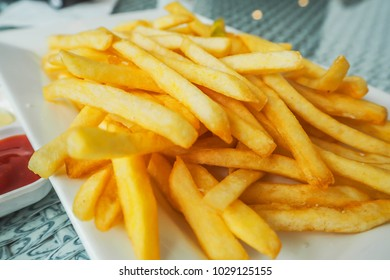 French Fries serve on a white plate with ketchup.