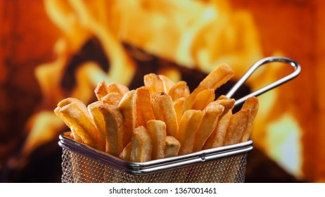 French fries served in metallic mesh recipient resembling the frying basket - in front of fire flames background