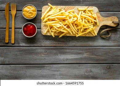 French fries served on cutting board on wooden table top-down copy space