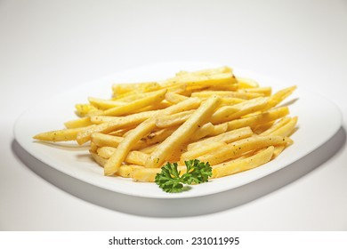 French Fries served on white plate, decorated with a branch of parsley.
