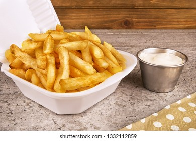 French fries in a take out container with a bowl of mayonnaise on a concrete texture table in background.