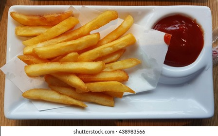 French fries in a white dish With Ketchup