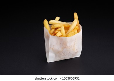French fries in a white paper box on black background.