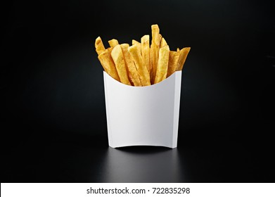 French fries in a white paper box isolated on black background. Front view.