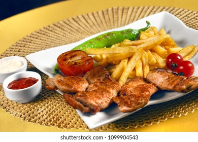 French fries,chiken kebab,tomatoes and peppers on the grill