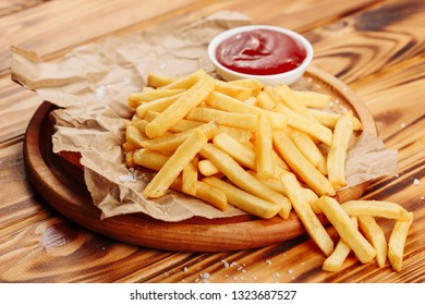 French fry Potato Snack Food Ketchup Side View. Golden Fries Meal on Wooden Rustic Board. Fresh Fast Cooked Crispy Dish of Yellow Chip Snack. Closeup Fatty Salted Dinner Portion on Paper