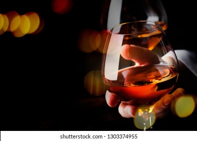 French glowing cognac glass in hand on the dark bar counter background, copy space, selective focus