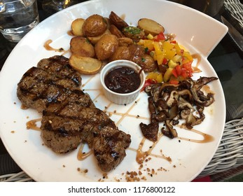 French Gourmet Cuisine at French Restaurant, Steak Bavette D'Aloyau D'Aubrac Served with Potatoes, Colorful Vegetables, and Sautéed Shiitake Mushrooms With Beautiful Presentation on  a White Plate
