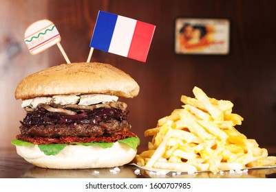 French Hamburger on wooden table served with french fries