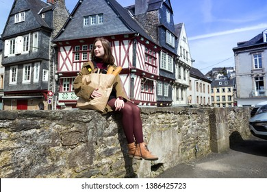 French happy smiling girl with baguettes on the background of  old colombage houses. Morlaix, France