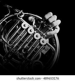 French horn music instrument Close up hand isolated on black background