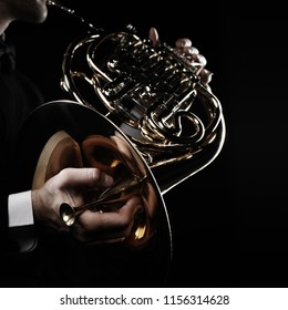 French horn player hands. Hornist playing brass orchestra music instrument closeup isolated