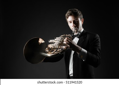 French horn player playing music instrument Man hornist classical musician