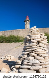 French island Ile de Re - The lighthouse Phare des Baleines at the coast with stacked stones in front