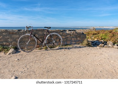 French landscape - Bretagne. Old bicycle with a beautiful rocky beach and view over the sea.