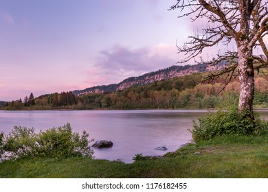 French landscape - Jura. View over the lake of Ilay in the Jura mountains (France) at sunset with rock in the foreground.